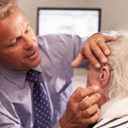 Doctor fitting a senior female patient with a hearing aid