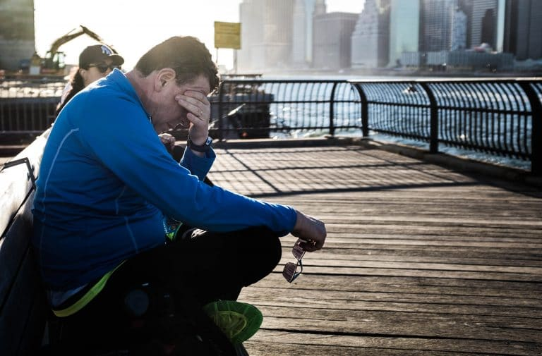 Man sitting on a pier rubbing his eyes out of exhaustion