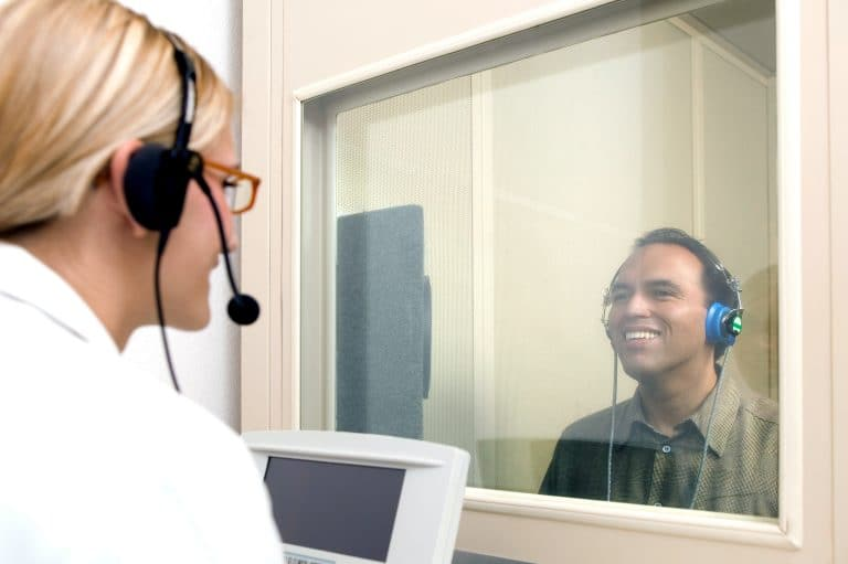 Man getting a hearing test in a hearing booth with an audiologist on the other side of the booth's glass