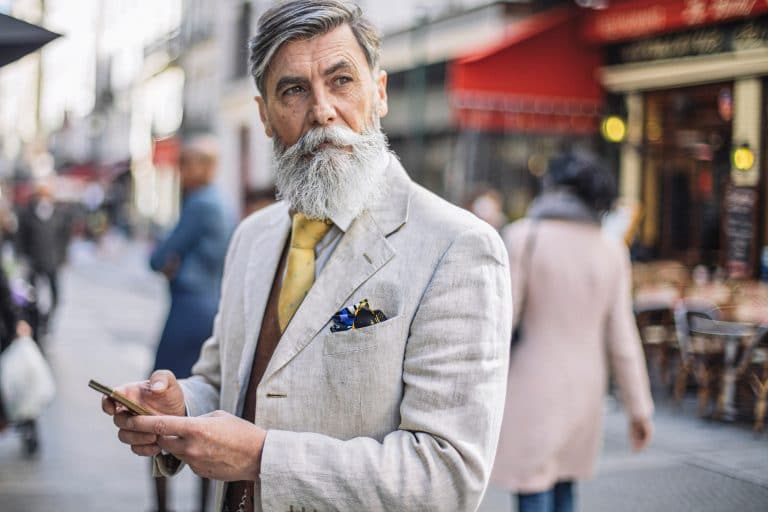 Older man in a suit standing in public