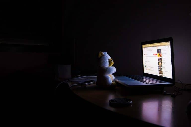 Teddy bear in darkened room facing computer screen