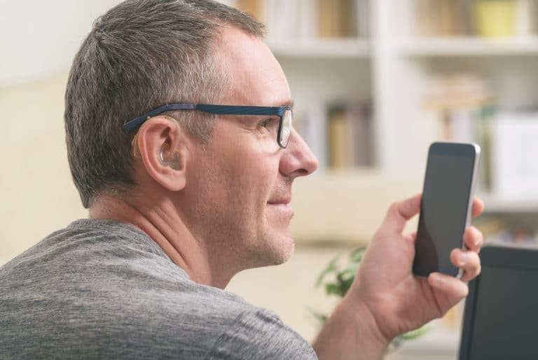 Man with a hearing aid using a phone.