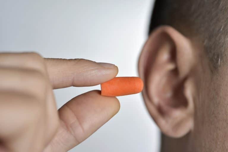 man putting earplugs into his ear.